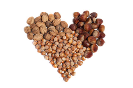 seeds of various: heart consists of hazelnuts, walnuts and chestnuts, isolated on white