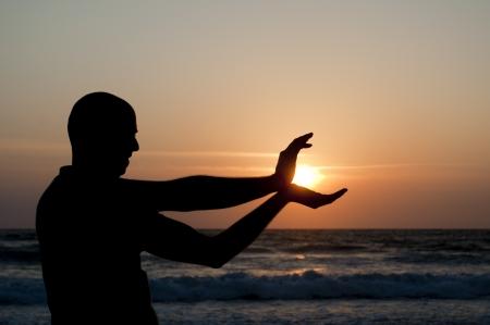 Man Silhouette unter der Sonne am Strand bei Sonnenuntergang Lizenzfreie Bilder