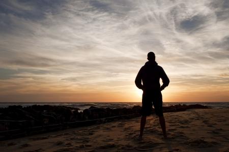 horizonte: Hombre de pie mirando la puesta de sol en la playa