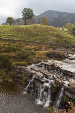 small waterfall in the mountains with green grass Stock Photo