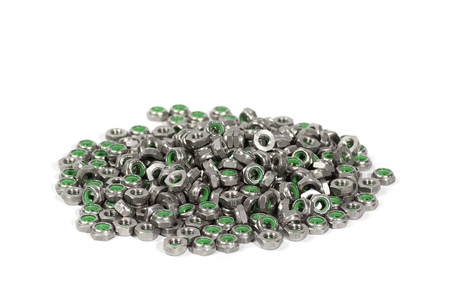 heap of metal nuts with green interior, stacked, isolated on white photo
