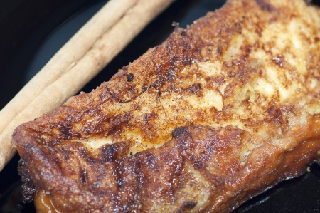 French toast, torrijas, and cinnamon stick on a black plate Stock Photo