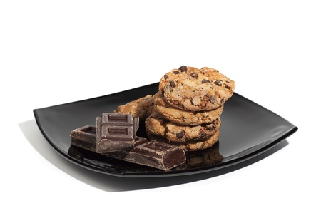 Cookies and chocolate pieces on black plate, isolated on white background photo