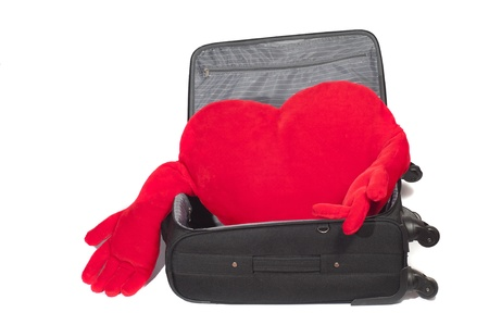 Red heart-shaped stuffed inside a suitcase photo