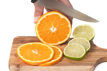 hand cutting orange and lime slices on a wooden board, isolated en white photo