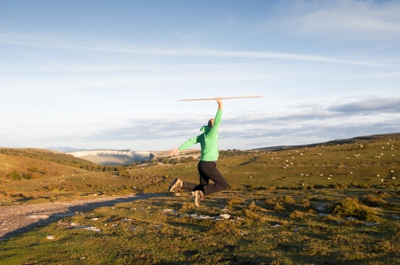 Young man jumping in the meadows photo