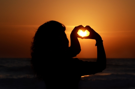 silhouette of a woman with her hands forming a heart, at sunset on the beach photo
