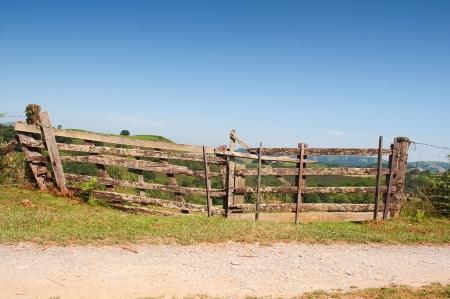 wicket gate: rustic wooden barrier un a green field