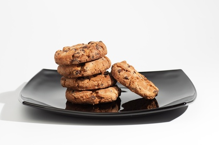 Some delicious chocolate cookies on a black plate isolated on white background