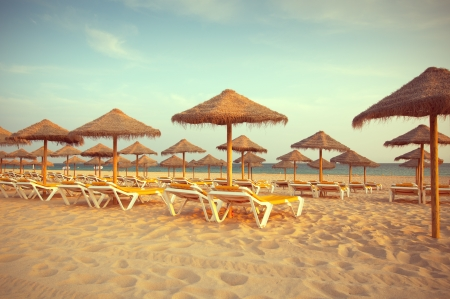 Empty deck loungers in the beach at sunset. Paradise in Algarve, Portugal Stock Photo