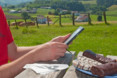 man using a tablet while a breakfast outdoor, rural setting