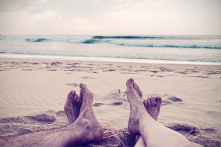 piernas hombre: La mujer y el hombre (piernas y pies) en la playa, estilo vintage Foto de archivo