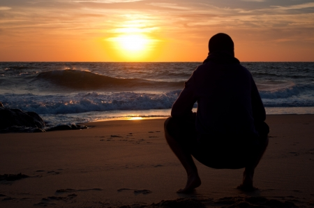 Man looking to the horizon at the beach, at sunset Stock Photo