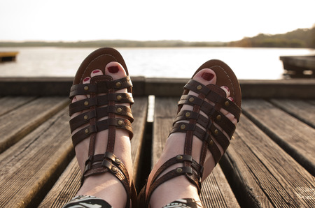 Woman feet in sandals and red nails in a wooden pier