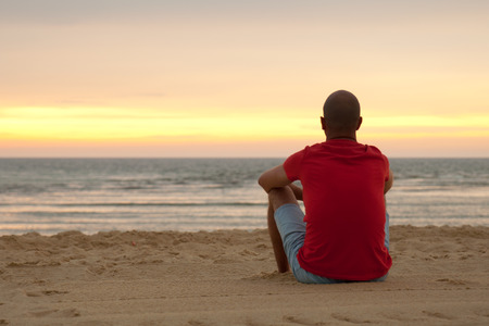 Young man sitting in the beach sand at sunset