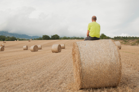 Young man in a field with straw bales. Resting on a bale Stock Photo