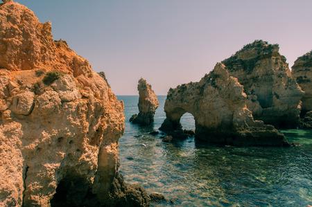 Algarve coast, Portugal. Rocks in the shoreline and blue water Stock Photo
