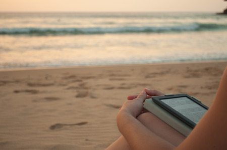 Woman reading in the beach with an ebook or tablet Stock Photo