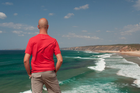 vilamoura: Young man looking at atlantic ocean in Algarve coast, Portugal. Summer vacations