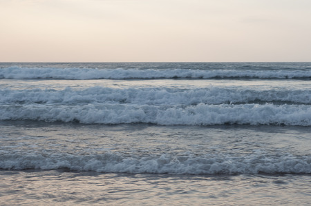 Little waves in the beach at sunset