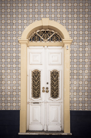 Old building facade, wooden door and tile wall in Ferragudo, Portugal Stock Photo