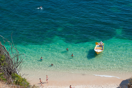 Algarve coast, Portugal. People and little boat in the blue water