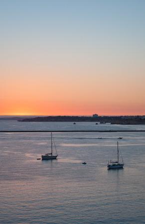 Portimao Blick auf die Stadt bei Sonnenuntergang. Boote in der Bucht in sonnigen Tag Lizenzfreie Bilder