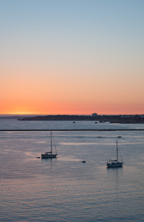 Portimao city view at sunset. Boats in the bay in sunny day