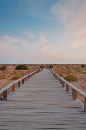 Wooden footbridge in the dunes, Algarve, Portugal, at sunset
