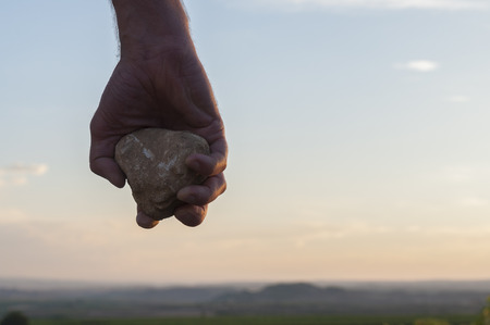 rock stone: Hand holding a stone.