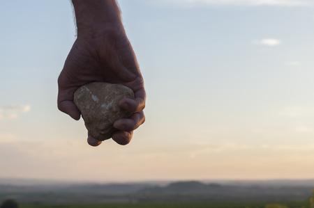 Ruka držící kámen. Reklamní fotografie