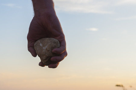 Hand holding a stone.
