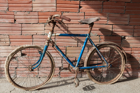 Antique or retro rusty bicycle in brick wall background. Child bike photo