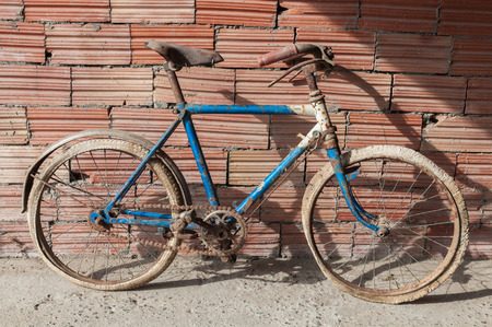 Antique or retro rusty bicycle in brick wall background. Child bike Stock Photo
