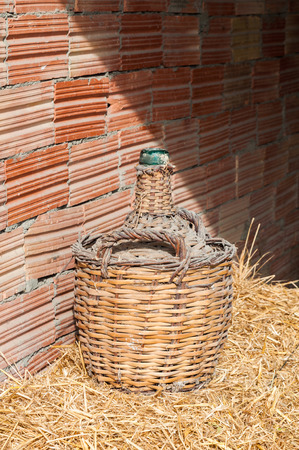 Old glass bottle lined with wood. Used to store wine Stock Photo