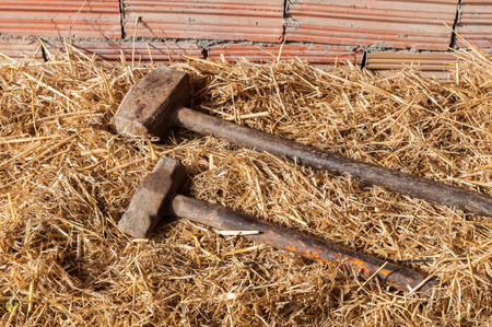 Two old iron hammer on dry grass