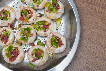 Preparing mushrooms stuffed with ham and pepper Stock Photo