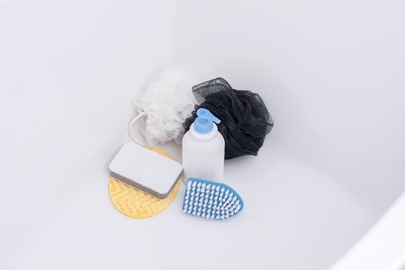 Brush, washcloth and rubber gloves in white bath. Things for cleaning. All in light blue on a white background.