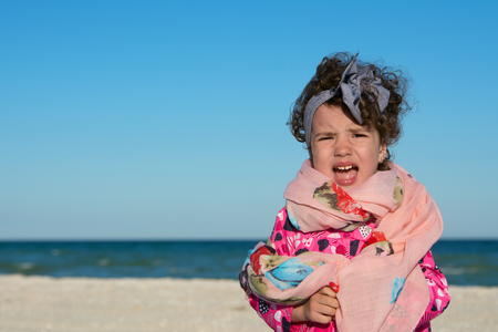 Little curly girl screaming and being capricious at the sea beach