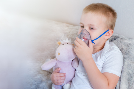 Little boy does inhalation at home with his toy