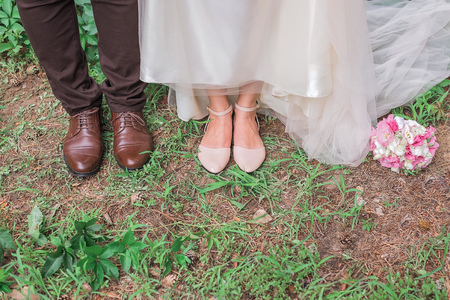 Cute cropped picture of grooms and brides shoes standing together on the grass