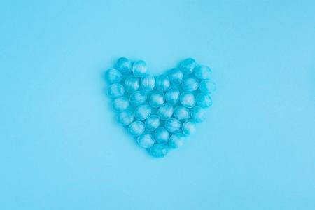 Round blue mint candy caramel on blue background makes heart shape Stock Photo