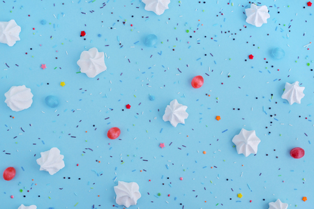 White meringues and colorful confetti on blue background, pattern.