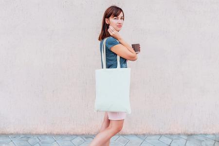 Junge Frau mit weißer Baumwolltasche und Papierkaffeetasse in ihren Händen.