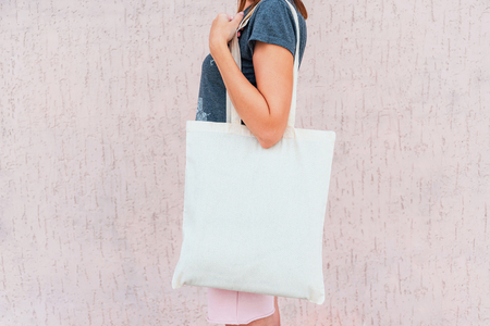 Young woman with white cotton bag in her hands. Mock up.