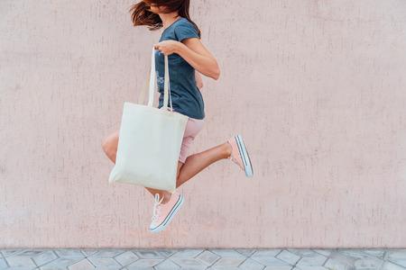 La jeune femme saute avec un sac en coton blanc dans ses mains. Maquette. Banque d'images