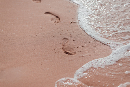 Foot prints on wet sand at the beach. Vacation concept. Top view.