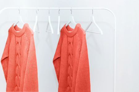 Living Coral knitted warm sweaters on hanger and many empty hangers. Creative and moody color of the picture. Color of the 2019 year.