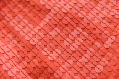 Coral shiny fabric with sequins, abstract background. Close-up. Banque d'images
