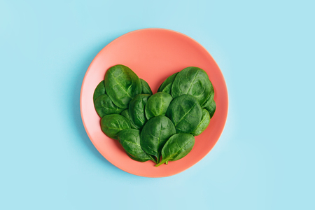 Green fresh vegetarian salad leaves shaped heart on coral plate on blue background. Healthy and zero waste life concept. Top view.